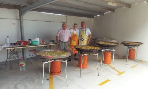 Three cooks while making 4 paellas for 130 people