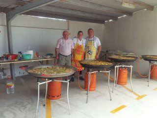 Three cooks while making paella for 130 people