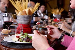 People around the table eating and drinking red wine in Rioja