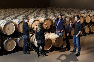 Four people tasting wine inside Pagos de Leza, Rioja winery's barrel cellar
