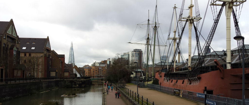 Panoramic view along Tobacco Dock in London, with old ship to the right and The Shard and skyline in the background