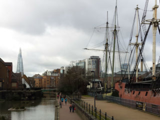Panoramic view along Tobacco Dock by the Thames, London, with old ship to the right and The Shard and skyline in the background